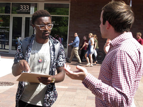 A University of Wisconsin student gets information about registering to vote from a NextGen America worker in Madison, Wis., in 2018.