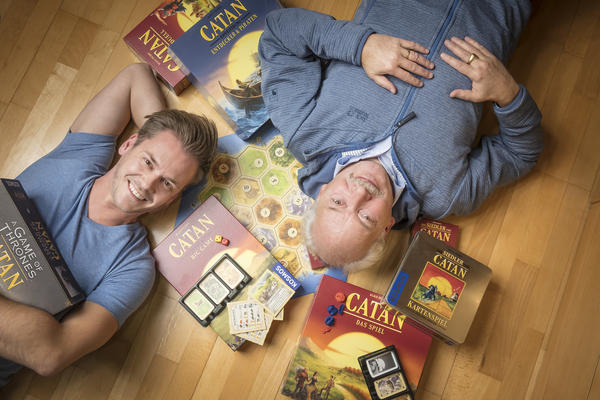 Klaus Teuber, creator of the popular board game Catan, with his son Benjamin Teuber, a managing director at Catan Inc. Celebrating the 25th anniversary of the game's launch, the elder Teuber has released an autobiography, <em>My Way to Catan</em>.