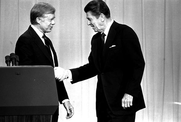 In this Oct. 28, 1980 file photo, President Jimmy Carter, left, and Republican presidential candidate Ronald Reagan, shake hands in Cleveland, Ohio, before debating before a nationwide television audience.