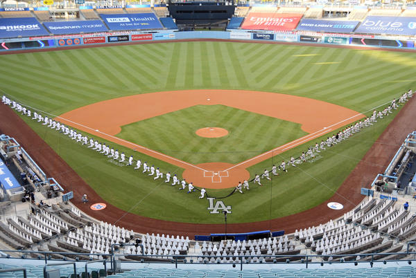 Members of the Los Angeles Dodgers and the San Francisco Giants kneel prior to the national anthem before their game at Dodger Stadium on July 23, 2020 in Los Angeles, California. (Harry How/Getty Images)
