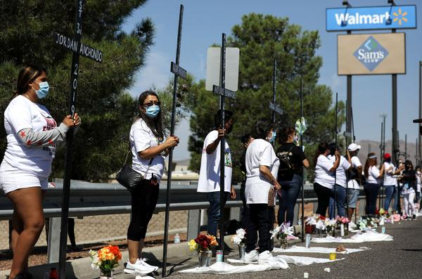 Mourners hold 23 crosses Monday in front of a Walmart honoring those killed in the 2019 attack in El Paso, Texas.