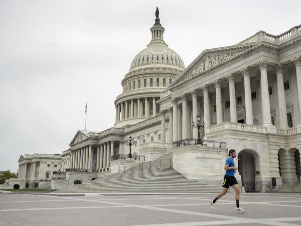 A man with a mask depicting American flags jogs past the U.S. Capitol in April. More than three-quarters of respondents to the NPR/Ipsos poll support enacting state laws to require mask wearing in public at all times.