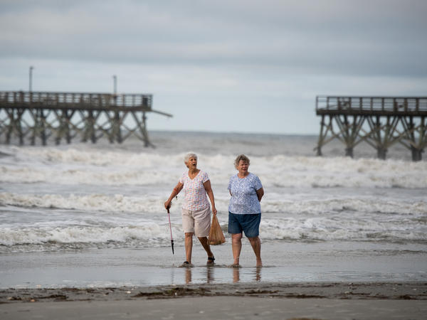Mary McCants (left) and Amy Garrett walk near a damaged pier the morning after Hurricane Isaias came through late Monday night in North Myrtle Beach, S.C. Hurricane Isaias was downgraded to a tropical storm Tuesday after making landfall overnight as a Category 1 hurricane in North Carolina.