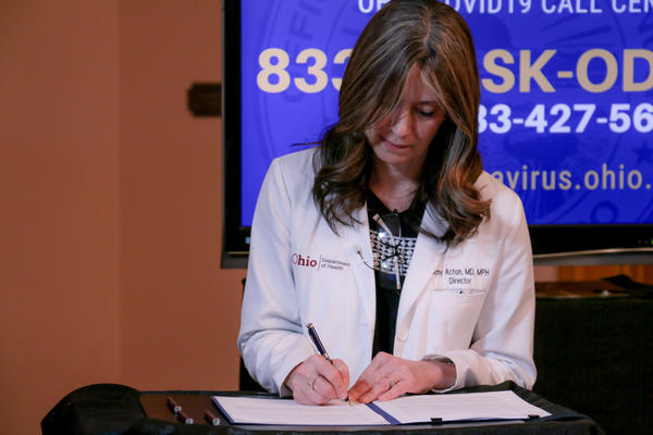 "Dr. Amy Acton signs ""Stay At Home"" order extension."