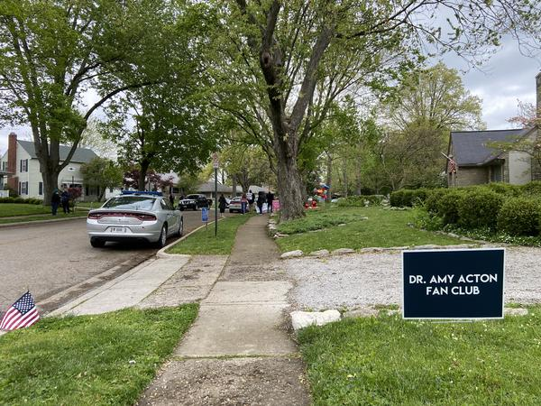 "A ""Dr. Amy Acton Fan Club"" sign posted down the street from Acton's house where a group of demonstrators gather."