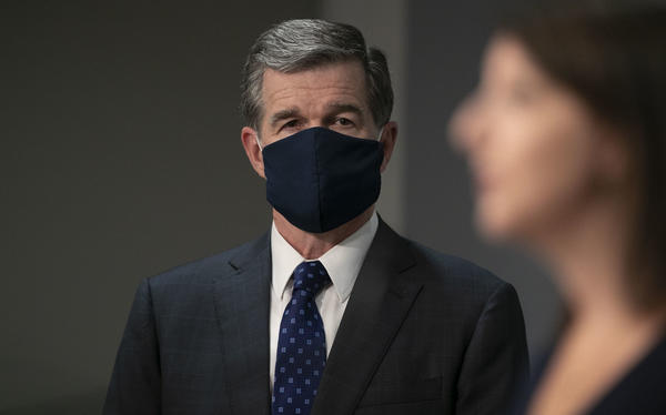 North Carolina Gov. Roy Cooper, left, listens as state Health and Human Services Secretary Mandy Cohen gives an update about the coronavirus pandemic on July 28 in Raleigh.