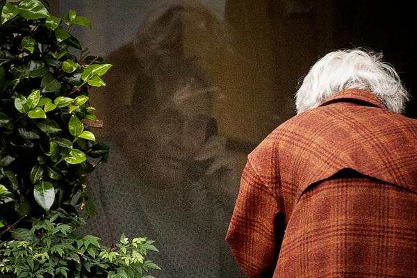 Dorothy Campbell talks to her husband, Gene Campbell, on the phone through his window at the Life Care Center of Kirkland , WA on March 5, 2020, because she was not allowed inside the facility.