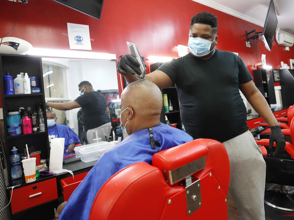 Wilkin Soto works on a customer at the Castillo Barbershop, in Lawrence, Mass., on June 5. The pace of hiring has slowed from June, when employers added a record 4.8 million jobs.