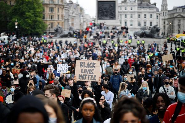 Activists, some wearing face coverings or face masks as a precautionary measure against COVID-19, hold placards as they attend a Black Lives Matter protest in Trafalgar Square in London on June 12, 2020, backdropped by the Houses of Parliament.  (Tolga Akmen/AFP via Getty Images)