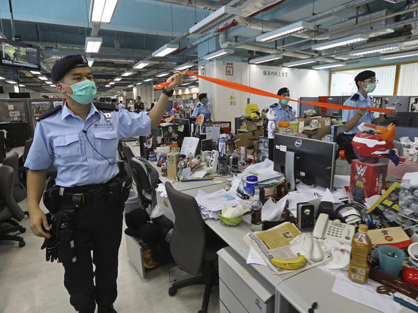 Hong Kong police officers search the newsroom of the <em>Apple Daily</em> newspaper Monday after arresting the paper's publisher, Jimmy Lai.