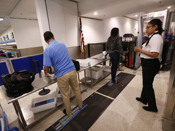 A Transportation Security Administration officer watches as travelers put their items through an X-ray machine in 2017 at Miami International Airport. The TSA says it's finding significantly more firearms in carry-on luggage despite a huge drop in air travel.
