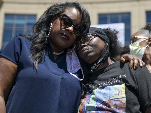 Elijah McClain's mother, Sheneen McClain (right), gets a hug from <strong></strong>Colorado state Rep. Leslie Herod in June as they stand with protesters outside the Aurora, Colo., police headquarters. On Tuesday, Sheneen McClain and Lawayne Mosley filed a federal civil rights lawsuit in their son's death.