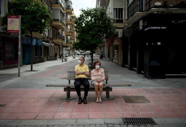 An elderly couple wearing face masks sits on a bench in Seville on May 7, 2020. (CRISTINA QUICLER/AFP via Getty Images)
