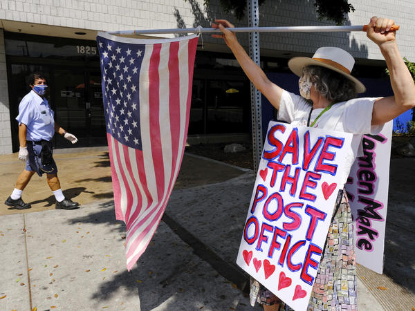 Erica Koesler of Los Angeles demonstrates outside a USPS post office as a postal worker walks by in the background on Saturday. The USPS has warned states coast to coast that it cannot guarantee all ballots cast by mail for the November election will arrive in time to be counted, even if mailed by state deadlines.