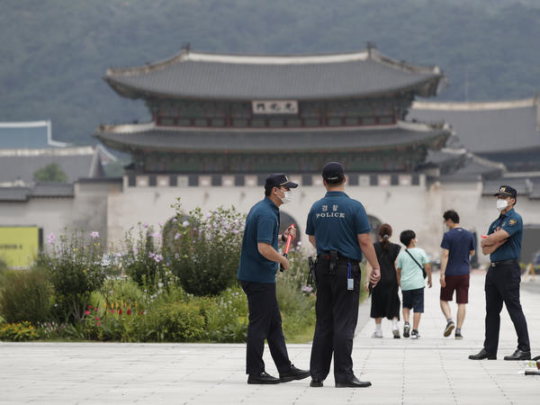Police officers and visitors wearing face masks to help protect against the spread of the coronavirus walk in downtown Seoul, South Korea, on Sunday.