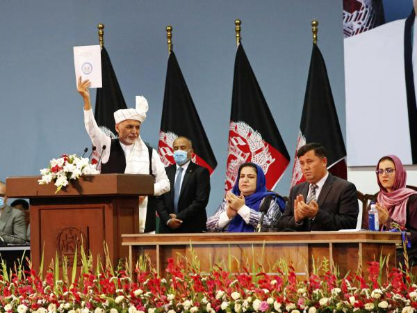 Afghan President Ashraf Ghani holds up a resolution on the last day of a traditional council known as a Loya Jirga, in Kabul, Afghanistan, Aug. 9. The council concluded with hundreds of delegates agreeing to free 400 Taliban members, paving the way for an early start to negotiations between Afghanistan's warring sides.