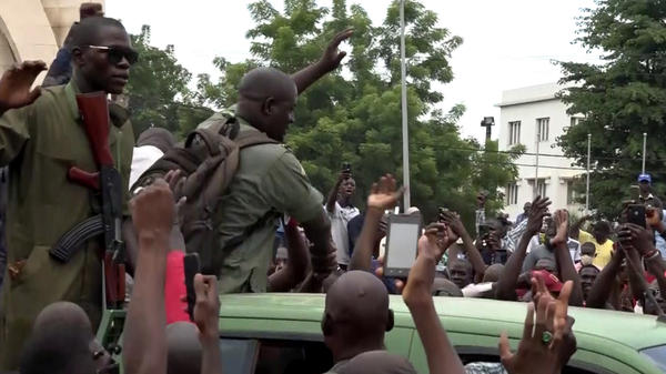 In a screen grab captured from a video, soldiers on a military vehicle are greeted by citizens Tuesday at Independence Square in Bamako, Mali. Soldiers staged a mutiny, and reportedly detained President Ibrahim Boubacar Keita.