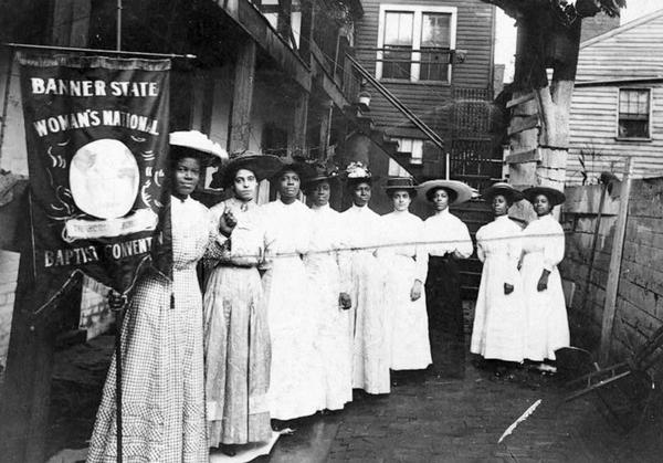 Nannie Helen Burroughs (left) was an educator and activist who fought for civil and women's rights, including women's suffrage. Here she and a group of women are posing with a holding a Woman's National Baptist Convention banner. (c 1910)