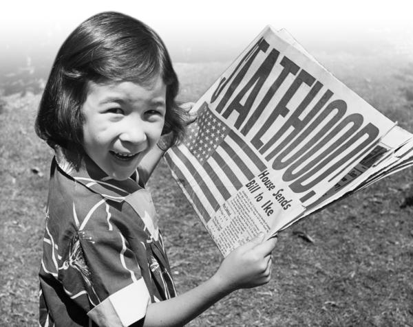 "Six-year-old Mary ""Dodie"" Brown holds a copy of the 1959 special Hawaii statehood edition of the Honolulu Star-Bulletin."