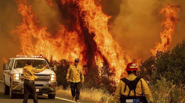 Flames from the LNU Lightning Complex fire leap above a road Sunday as firefighters work to contain the blaze in Lake County, Calif.