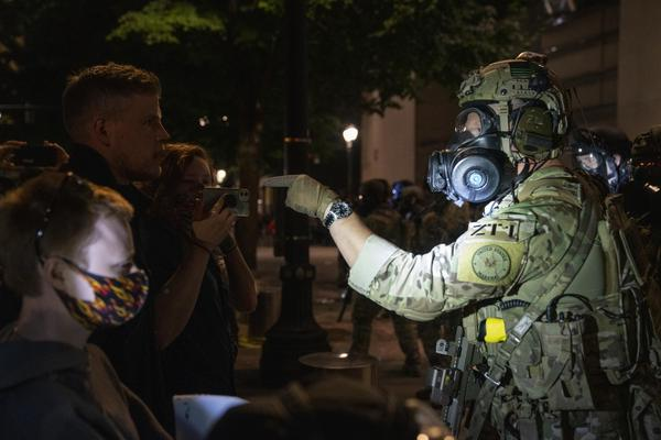 Protesters demonstrate against racism and police violence in front of the Mark O. Hatfield federal courthouse. Earlier in the night, federal law enforcement officers shot a demonstrator in the head with a less-lethal impact munition, causing severe injury.