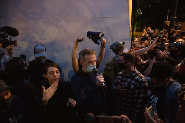 A demonstrator holds a police hat above Mayor Ted Wheeler's head at a protest against police brutality and systemic racism in Portland, Ore., July 22, 2020. Wheeler has faced criticism for the Portland Police Bureau's use of force against demonstrators long before federal officers' arrival.