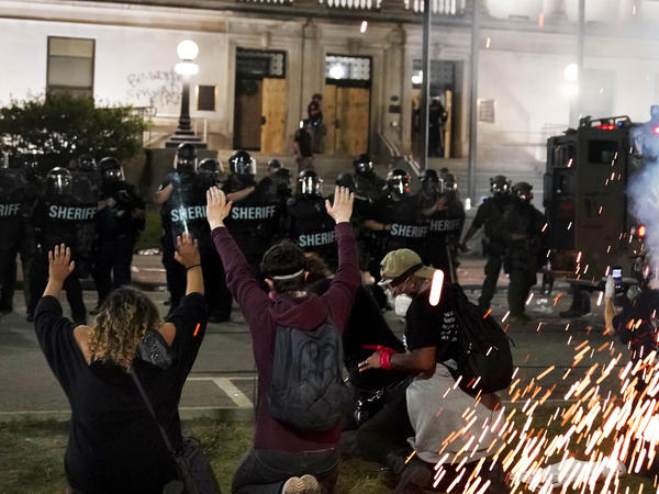 Police attempt to push back protesters outside the Kenosha County Courthouse late Monday in Kenosha, Wis. Protests continued for a second night after the police shooting of Jacob Blake.