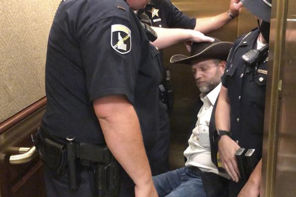 After he refused to stand when asked, anti-government activist Ammon Bundy was wheeled into an elevator in a chair, following his arrest at the Idaho Statehouse in Boise on Tuesday.