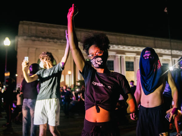 Demonstrators raise their fists in the air on Tuesday in Kenosha, Wis. It was the third night of protests in the city following the police shooting of Jacob Blake on Sunday.