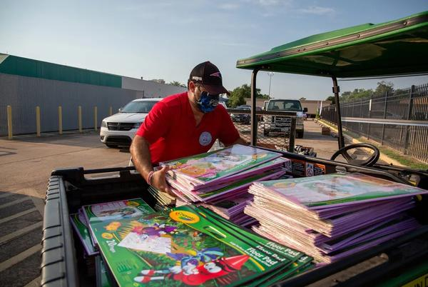 Supplies are loaded into vehicles during a drive-through school supply giveaway at Raul Yzaguirre School for Success in Houston.