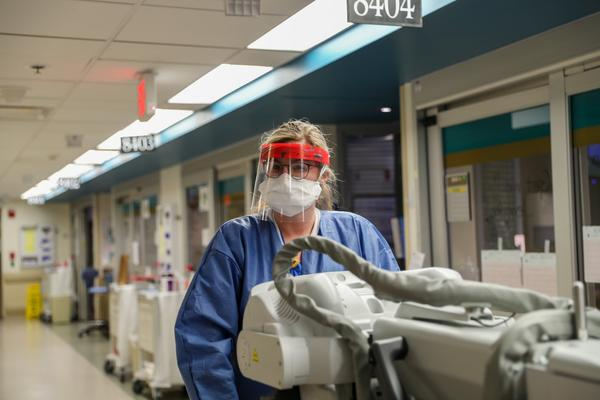 A hospital worker rolls equipment through the intensive care unit at Barnes Jewish Hospital in April 2020. St. Louis hospitals saw 71 new admissions of people sick with the coronavirus on Monday.