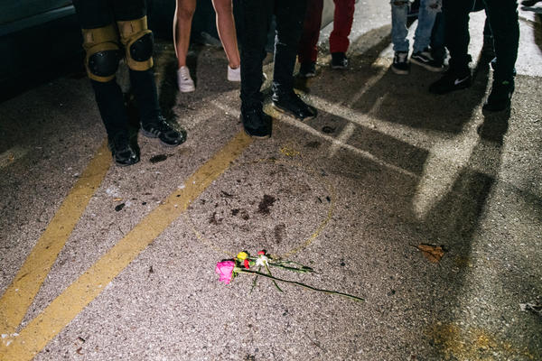 Demonstrators revisit the site where a protester was killed in Kenosha, Wis. Earlier in the week, Kyle Rittenhouse shot and killed two protesters. He was charged on Thursday with six criminal counts, including first-degree intentional homicide.