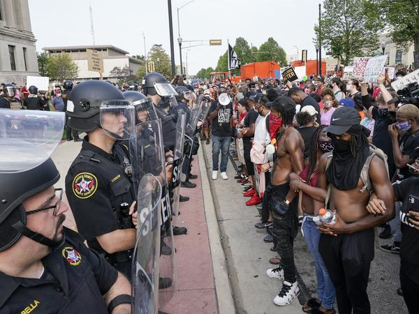 Protesters link arms in front of a police line outside the Kenosha County courthouse on Monday, Aug. 24, 2020. Kyle Rittenhouse, 17, has been charged with allegedly killing two protesters in Kenosha this week.