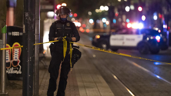 A Portland police officer ties a police line around the scene of a fatal shooting in Portland Saturday. It's the latest incident after weeks of Trump supporters clashing with counterprotesters.