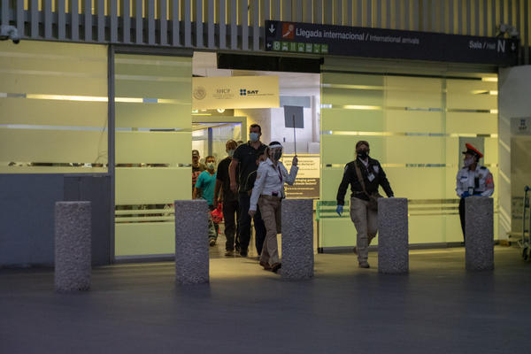 Expelled migrants enter Mexico through a gate tucked away in the second terminal of Mexico City International Airport on July 9, 2020 after being flown out of the U.S. from either San Diego, California or Brownsville, Texas by Immigration and Customs Enforcement.