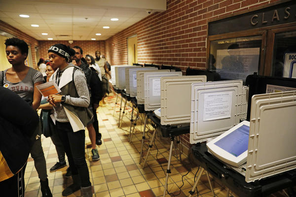 Voters in Atlanta wait in line to cast their ballots on Election Day in 2018. A federal judge has ruled that electronic voting machines like the ones shown must be replaced after the 2019 elections.