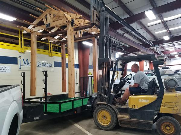 An employee with the city of Montgomery, Ohio lowers a wooden pergola onto a flatbed trailer. It will be transformed into a patriotic park scene with bunting, banners and flags. Many participants in the reverse parade are repurposing previous years' floats because of COVID-19 restrictions on gathering.