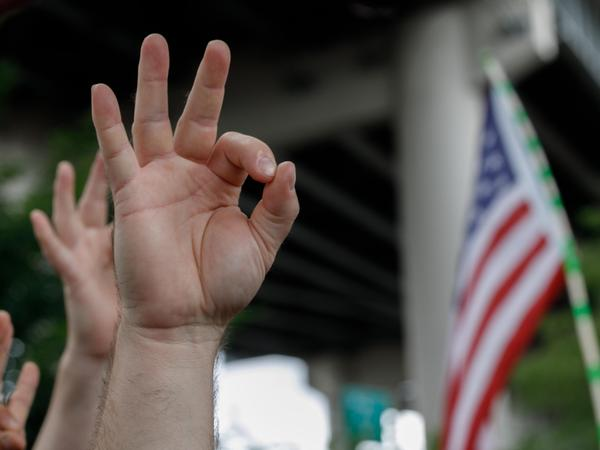 A demonstrator makes the OK hand gesture believed to have white supremacist connotations during the End Domestic Terrorism rally in Portland, Ore., on Aug. 17, 2019.