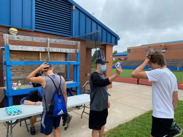 Coach Tim Wall conducts temperature scans of each player before practice begins at Lake Norman High School.