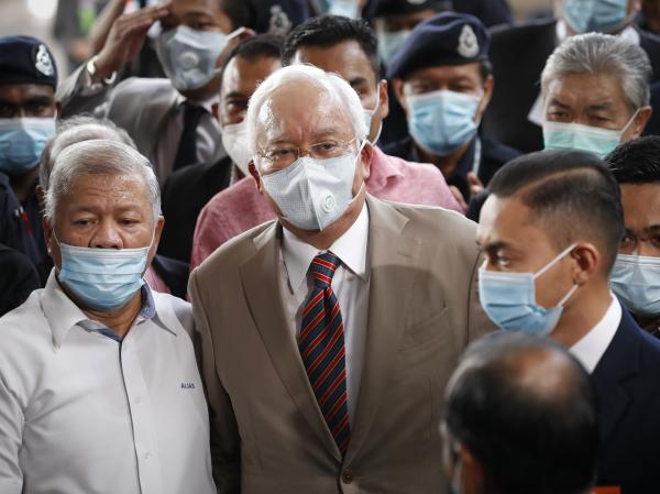 Former Malaysian Prime Minister Najib Razak (center), wearing a face mask with his supporters, arrives at the courthouse in Kuala Lumpur, Malaysia, on Tuesday. Najib was found guilty of corruption in the first of several trials linked to the multibillion-dollar looting of the 1MDB state investment fund.