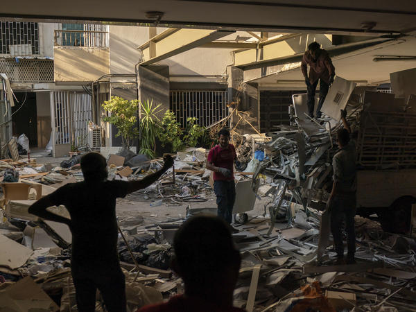 Workers remove debris from a hospital that was heavily damaged in last week's explosion that hit the seaport of Beirut.