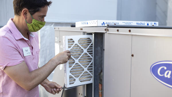 Mark Marston slides a MERV 13 air filter into the HVAC system outside Basics Fitness Center in Portland, Maine, on July 21. The gym bought these filters and made other changes to its ventilation, including bringing in more outside air, to help reduce the spread of the coronavirus.