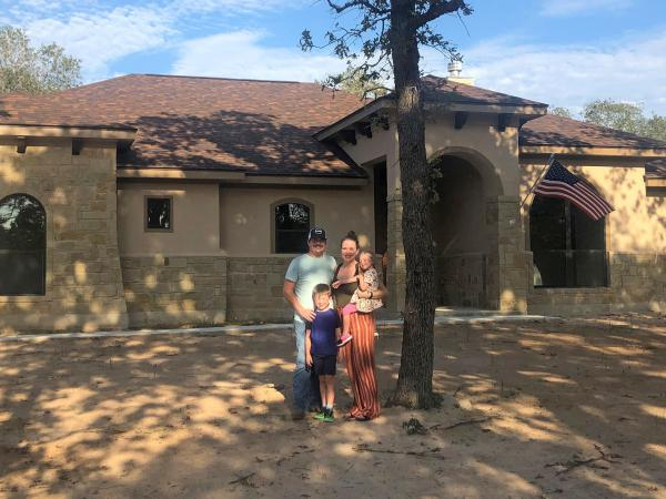 Caroline Wells and her family at their new home outside San Antonio. The builders just finished it so the yard has yet to be planted, but the couple are looking forward to letting the kids run out their energy with a lot more outdoor space than they had at their home in the city.