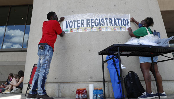 Aetry Jones, left, and Caerry Rigbon tape up a voter registration sign on Dallas City Hall before a Juneteenth 2020 celebration and protest against police brutality in Dallas, Friday, June 19, 2020. Juneteenth marks the day in 1865 when federal troops arrived in Galveston, Texas to take control of the state and ensure all enslaved people be freed. (AP Photo/LM Otero)