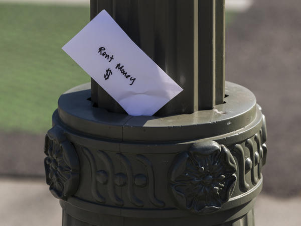 "A paper envelope written with the words ""Rent Money $"" is left tucked in a lighting pole in April in the Boyle Heights area of Los Angeles. Amid massive job losses due to COVID-19, California Gov. Gavin Newsom signed an extended eviction moratorium on Monday."