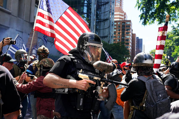 A member of the Proud Boys fires a paint ball gun into a crowd of anti-police protesters as the two sides clashed on August 22, 2020 in Portland, Oregon. (Nathan Howard/Getty Images)