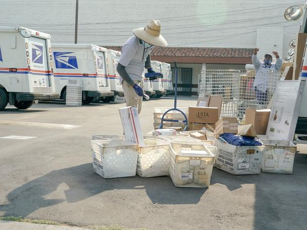 Postal workers sort, load and deliver mail at a U.S. Postal Service location last month in Los Angeles.