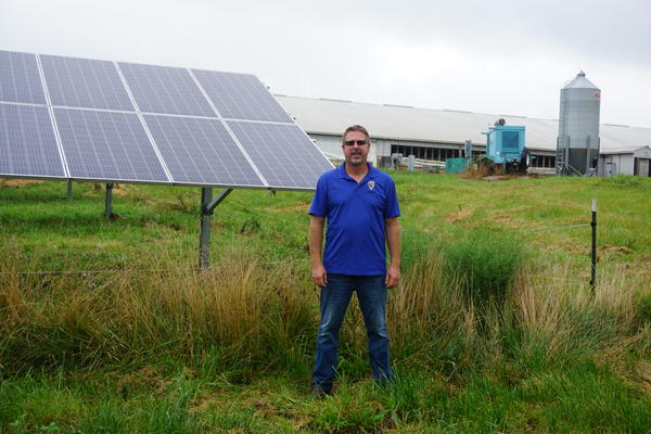 Missouri Farmer Chris Bohr stands next to his solar panels in front of his hog barn. He received a USDA REAP grant to help pay of the project.