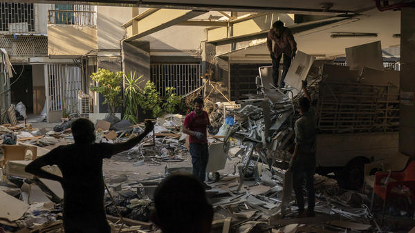 """Workers remove debris from a hospital that was heavily damaged in last month's explosion in Beirut. Lebanon's interim health minister, Hamad Hasan, told local media last month that the health system was """"on the brink"""" of being overwhelmed because of the needs of blast victims and COVID-19 patients."""