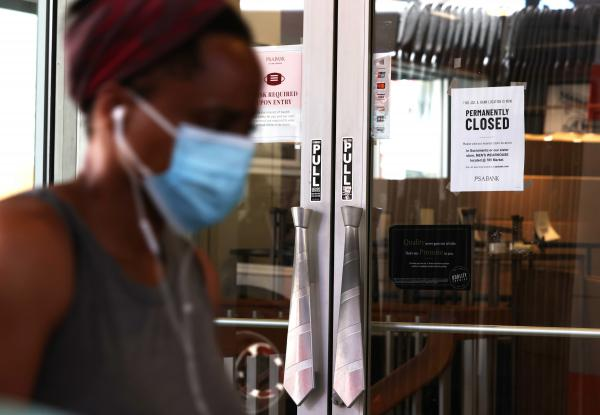 A pedestrian walks by a Jos A. Bank clothing store that is closing on August 03, 2020 in San Francisco, California. (Justin Sullivan/Getty Images)